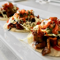 Spicy Pork Taco grilled spicy marinated pork, pico de gallo, shredded cabbage and maple gochujang sauce
